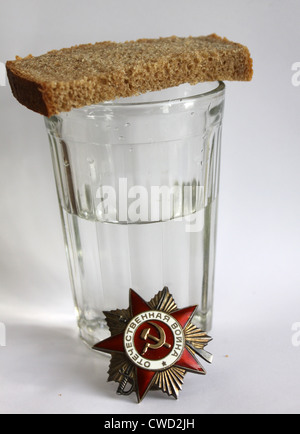 The order 'Great Patriotic war' and glass with vodka and piece of bread - Stock Photo