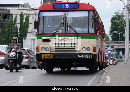 Packed number 15 bus crests bridge in heavy morning traffic, Sukhumvit Road, Bangkok. - Stock Photo