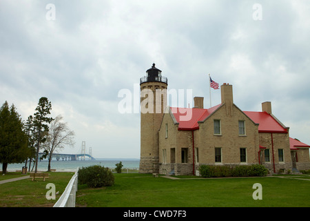 Old Mackinac Point Lighthouse in Mackinaw City, Michigan with the Mackinac bridge in the background - Stock Photo