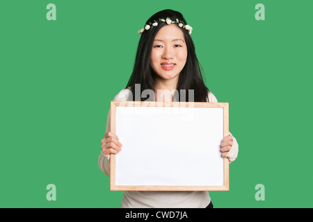 Portrait of a young woman holding a blank whiteboard over green background - Stock Photo
