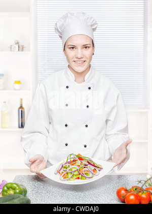 Young chef offering vegetarian meal in kitchen - Stock Photo