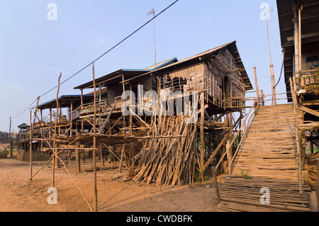 Horizontal wide angle view of the stilted grass houses of Kompong Khleang, the floating village on Tonle Sap Lake - Stock Photo