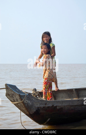 Vertical portrait of two young girls standing on a boat in Kompong Khleang, the floating village on Tonle Sap Lake - Stock Photo