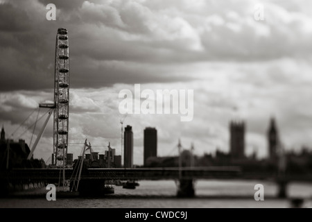 The London eye seen with the railway bridge. Shot with a tilt-shift lens. Westminster and the city is in the background. - Stock Photo