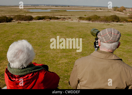 An elderly man and woman use a telescope and binoculars to watch birds at Cliffe Pools nature reserve Kent, UK. - Stock Photo