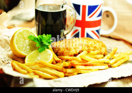 Traditional fish and chips with lemon and dark beer in newspaper wrapping - Stock Photo