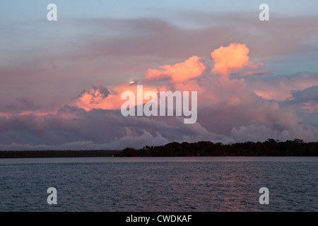 Early morning light reflects off clouds just as the moon is beginning to set. - Stock Photo