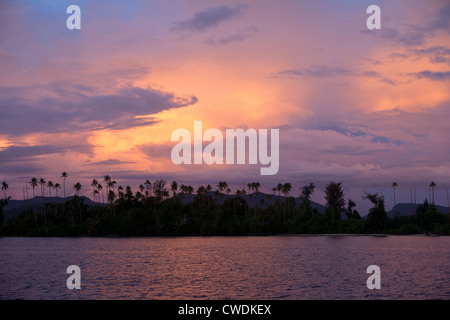 Early morning light reflects off clouds hanging over a low lying island amid the Solomon Archipelago. - Stock Photo