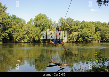 Man having fun on a rope by the river in the Lot Region of South West France Europe - Stock Photo