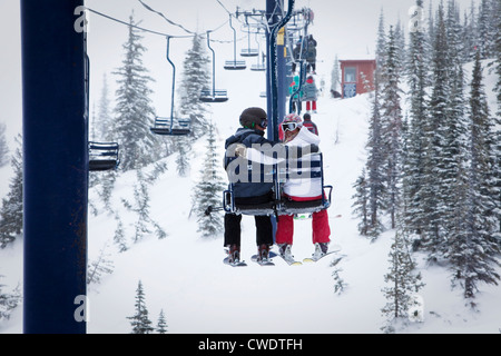 Two young adults smile while sitting on a double chairlift at a ski resort in Idaho. - Stock Photo