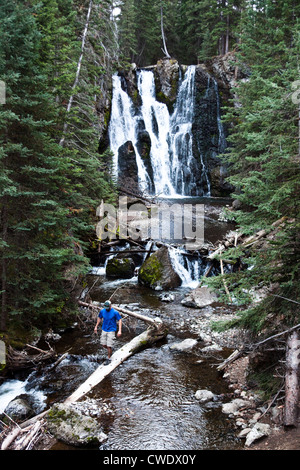 A athletic man hiking walks across a fallen log next to a waterfall in Montana. - Stock Photo