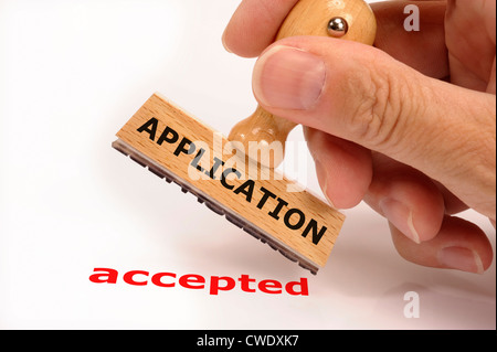 rubber stamp in hand marked with application accepted - Stock Photo