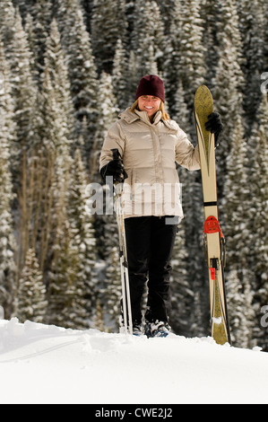 A smiling woman standing with skis in front of snow covered trees, San Juan National Forest, Silverton, Colorado. - Stock Photo