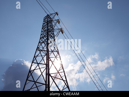 power grid pylon over sunny sky with clouds - Stock Photo