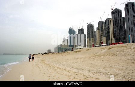 Dubai, the beach in front of the construction site at the Dubai Marina - Stock Photo