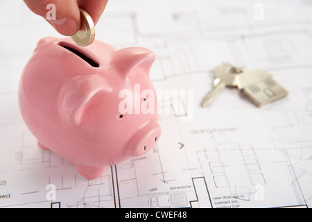 Piggybank with house plans and keys - Stock Photo