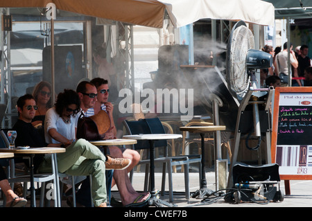 Customers at a bar in the Place de la Comedie in Montpellier cool off in front of a large fan with a cooling mist - Stock Photo