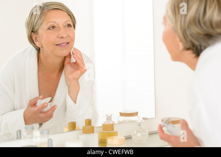 Pretty senior woman in bathroom looking at herself in mirror - Stock Photo