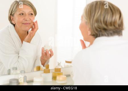 Senior woman looking in bathroom mirror applying anti-wrinkles face cream - Stock Photo
