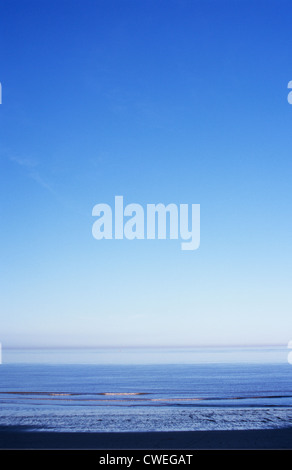 Flat calm blue sea with gentle rippling waves breaking on beach under wide blue sky - Stock Photo