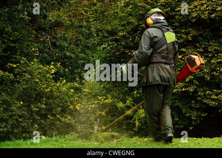 An agricultural worker trimming the brush with a petrol strimmer - Stock Photo