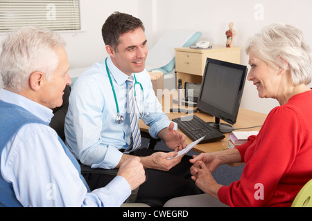 British GP talking to senior couple in surgery - Stock Photo