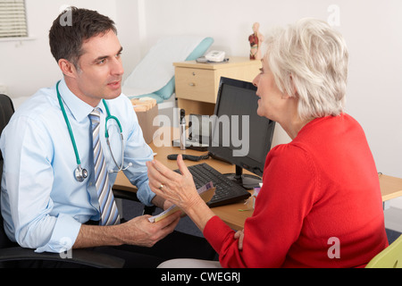 British GP talking to senior woman in surgery - Stock Photo