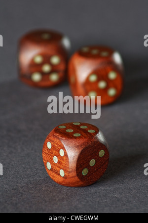 three wooden dice on a grey neutral background - Stock Photo