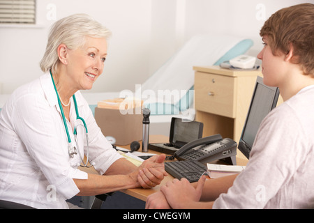 British GP talking to young male patient - Stock Photo