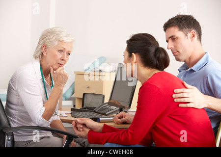 British GP talking to anxious couple in surgery - Stock Photo
