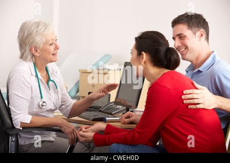 British GP talking to happy couple in surgery - Stock Photo