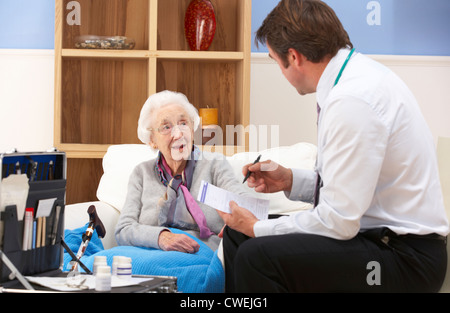UK GP visiting senior woman at home - Stock Photo