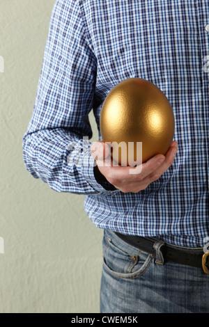 Cropped Studio Shot Of Man Holding Golden Egg - Stock Photo
