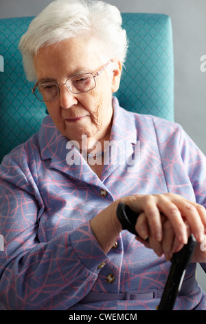 Unhappy Senior Woman Sitting In Chair Holding Walking Stick - Stock Photo
