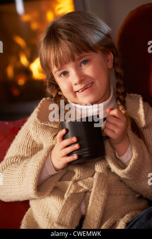 Young Girl Relaxing With Hot Drink By Cosy Log Fire - Stock Photo