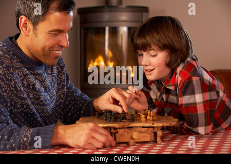 Father And Son Playing Chess By Cosy Log Fire - Stock Photo