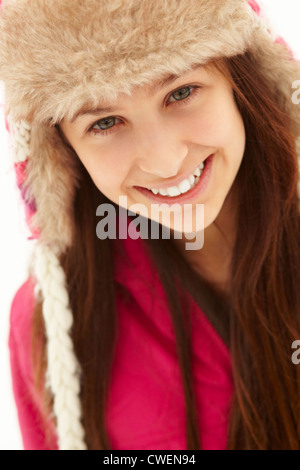 Portrait Of Teenage Girl In Snow Wearing Fur Hat - Stock Photo