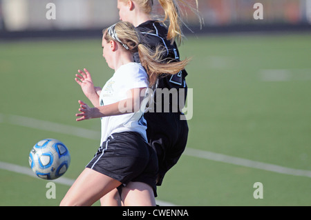 Soccer Players turn together in reaction to the flight of the ball during a high school soccer match. - Stock Photo