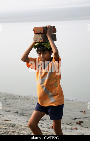 Child workers carry bricks carrying it on his head in Sonakhali, West Bengal, India on January 17, 2009. - Stock Photo