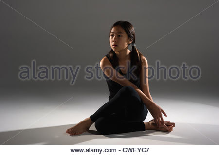 Young Asian girl sitting doing yoga stretches. - Stock Photo