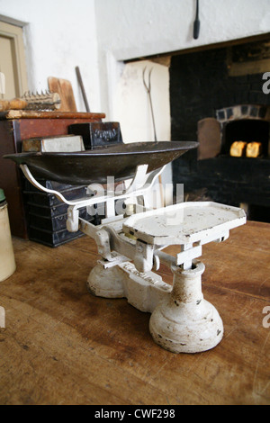 Old fashioned kitchen weighing scales in a rustic kitchen with a coal fired grate in the background - Stock Photo