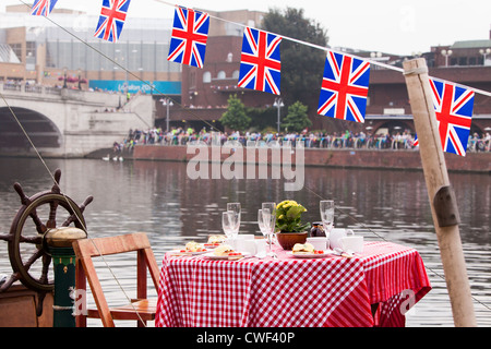 Popping the cork on a bottle of celebratory champagne just in time for Royal Barge, Gloriana to pass by Kingston - Stock Photo