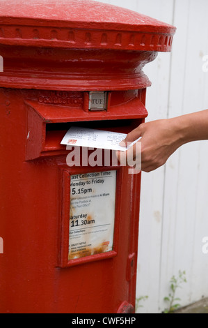 person posting or mailing a holiday post card into a red royal mail post box - Stock Photo