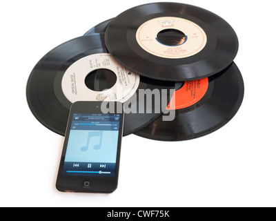 Records and iPod. An iPod sits on a pile of dusty 45rpm records. - Stock Photo