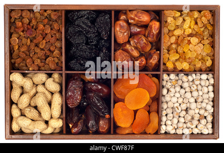 Assorted dried fruits in wooden box,isolated on white background.Raisin,prune,date,monkey-nut, apricot,nuts - Stock Photo