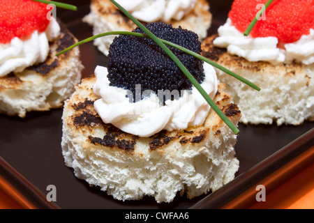 Red and black caviar canapés decorated with chives. - Stock Photo