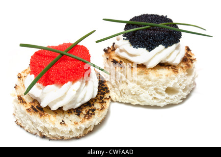 Red and black caviar canapés decorated with chives, on white background. - Stock Photo
