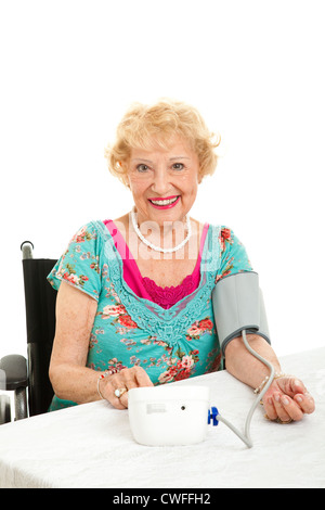 Senior woman taking he own blood pressure at home. Isolated on white background.  - Stock Photo