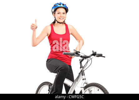 A bicyclist posing on a bicycle and giving a thumb up isolated against white background - Stock Photo