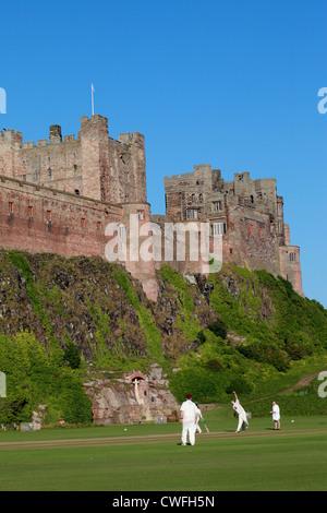 Cricket match taking place on ground below Bamburgh Castle, Northumberland UK - Stock Photo
